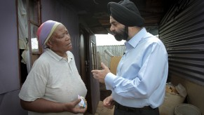 Ajay Banga, MasterCard Worldwide President and CEO (right), discusses the benefits of the South African Social Security Agency (SASSA) Debit MasterCard with Hilda Nkantini (left) at the Elias Motsoaledi settlement in Soweto outside Johannesburg. Nkantini is one of the nearly six million South Africans who now receive their social grant payments securely and conveniently by using the Debit MasterCard, which can also be used to pay for purchases, check balances and withdraw cash largely without incurring transaction fees. (Nadine Hutton/AP Images for MasterCard Worldwide)